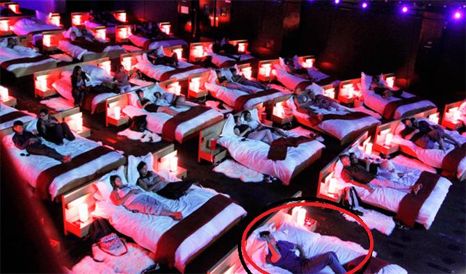 tek başına yataklı sinemaya giden erkek